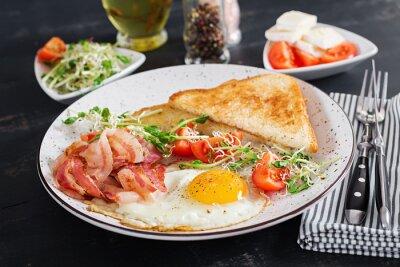 English breakfast - toast, egg, bacon and tomatoes and microgreens salad.