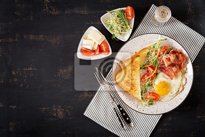 English breakfast - toast, egg, bacon and tomatoes and microgreens salad. Top view. Flat lay