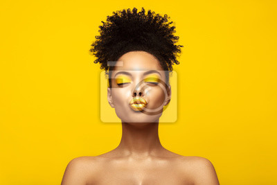 Plakat Enjoyed African American Fashion Model portrait . Satisfied Brunette young woman with afro hair style and closed eyes show kiss,creative yellow make up, lips and eyeshadows on colorful background.