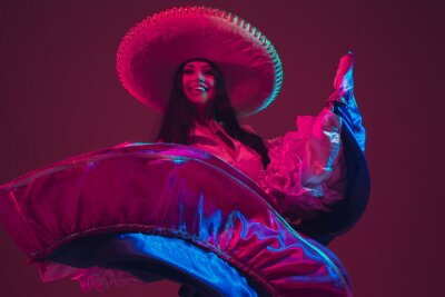 Plakat Fabulous Cinco de Mayo female dancer on purple studio background in neon light. Beautiful female model in traditional costume and sombrero dancing. Celebration, holiday, beauty and fashion concept.