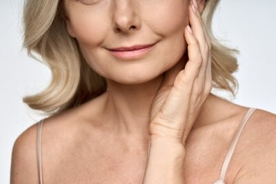 Plakat Face close up portrait of happy mid age 50 years old woman touching face with hand. Advertising of skin care anti wrinkle products for facial bottom part, lips, chin neck and decollete.