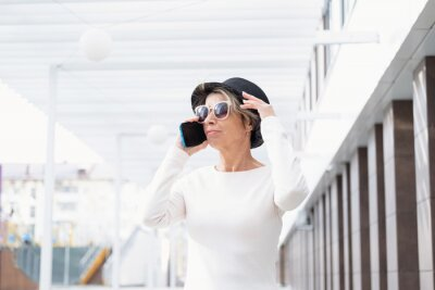 Plakat Fashion business senior attractive woman walking with phone in the city