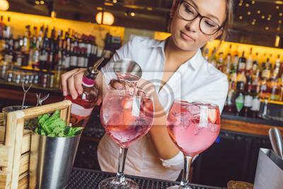 Plakat female beautiful smart bartender mixologist bar person makes prepares gin tonic cocktail drink pink mint fish bowl glass