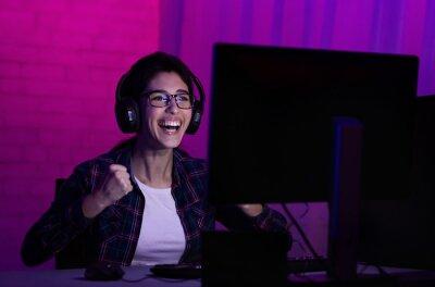 Plakat Female gamer win game, wearing headphones and rejoicing