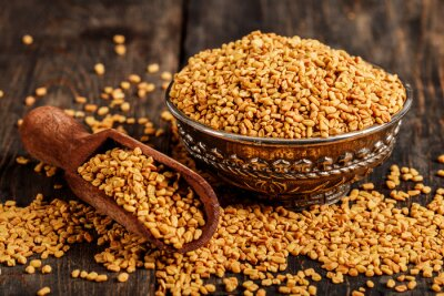 Plakat Fenugreek seeds on metal plate, spice, culinary ingredient. Fenugreek seeds in wooden spoon on textured background. Fenugreek seeds in a spoon and on a table.