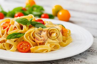 Fettuccine makaron w sosie pomidorowym z kurczaka, pomidory ozdobione bazylii na drewnianym stole
