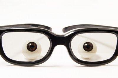 Figury oczu lub gałek ocznych znajdują się za okularami w czarnych oprawkach w lekko przyciemnionej szybie na białym tle. Zdjęcie koncepcyjne do okulistyki, optometrii, doboru okularów do poprawienia