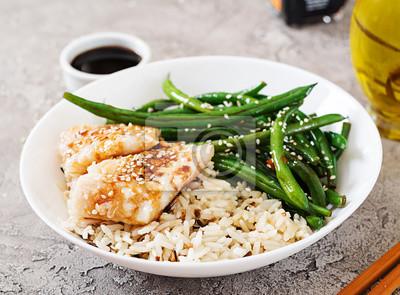 Filet rybny podawany z ryżem, sosem sojowym i fasolką szparagową w białym talerzu. Azjatyckie jedzenie.