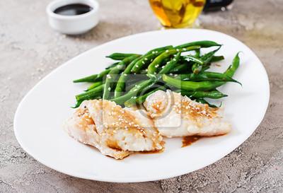 Filet rybny podawany z sosem sojowym i zieloną fasolką w białej płytce. Azjatyckie jedzenie.