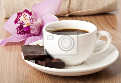 filiżanka kawy, czekolady i orchidea na tle drewniane