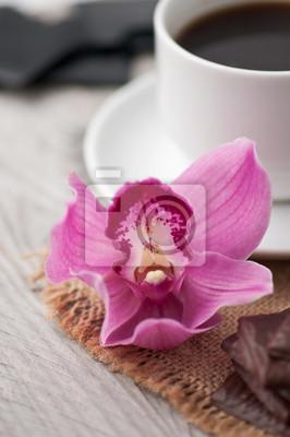 filiżanka kawy, czekolady i orchidei na drewnianym tle