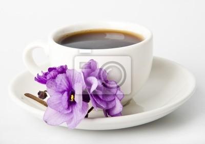 Filiżanka kawy i fiołków na białym stole