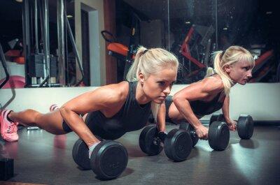 Plakat fitnes kobiety robi push up w siłowni
