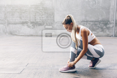 Plakat Fitness sport woman in fashion sportswear doing workout over gray wall