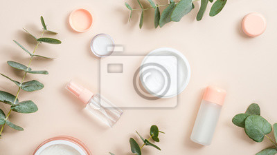 Plakat Flat lay composition with natural organic cosmetic products on beige background. Top view hand cream in jar, essential oil, skin lotion and eucalyptus leaves. Natural organic beauty product concept