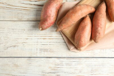 Plakat Flat lay composition with sweet potatoes and space for text on white wooden background