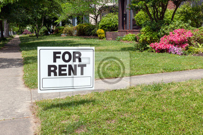Plakat FOR RENT sign posted in lawn advertising home for rent.