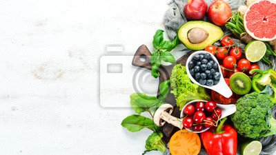 Plakat Fresh fruits and vegetables on a white wooden background. Top view. Free space for your text.
