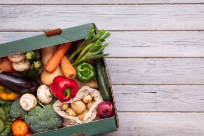 Plakat Fresh organic vegetable delivery box on a wooden background