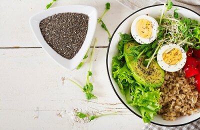 Fresh salad. Breakfast bowl with oatmeal, paprika, avocado, lettuce, microgreens and boiled egg. Healthy food. Vegetarian buddha bowl. Top view