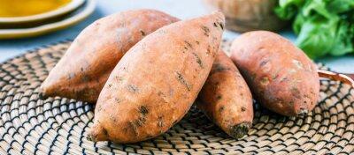 Plakat Fresh sweet potatoes on rustic background.