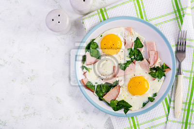 Fried eggs  with ham and spinach. Delicious English Breakfast. Brunch. Keto/paleo diet. Top view, overhead