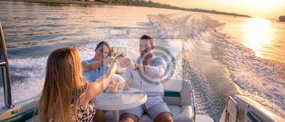 Plakat Friends are drinking on a boat in sunset