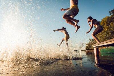 Plakat Friends having fun enjoying a summer day swimming and jumping at the lake.