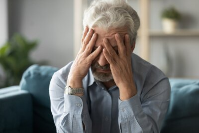 Plakat Frustrated unhealthy senior mature man touching head, having painful feelings sitting alone at home. Unhappy middle aged retired grandfather suffering from high blood pressure disease indoors.
