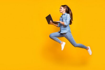 Plakat Full body profile photo of pretty business lady jump high holding notebook hands hurry work browsing laptop wear casual denim outfit white sneakers isolated yellow color background