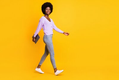 Plakat Full body profile photo of pretty dark skin person walking arm hold laptop isolated on yellow color background