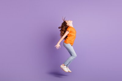 Plakat Full length body size view of attractive spprty girl jumping having fun dancing isolated over violet purple color background