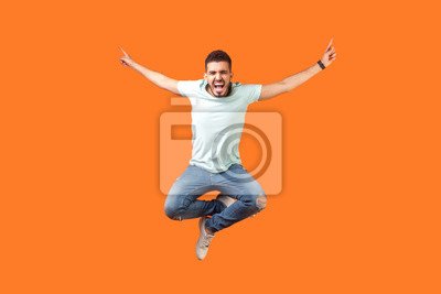 Plakat Full length of crazy overjoyed brunette man in white outfit jumping in air with raised hands, screaming loud for joy, feeling energetic and lively. indoor studio shot isolated on orange background