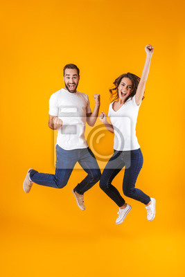 Plakat Full length photo of rejoicing couple screaming in surprise while jumping, isolated over yellow background