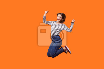 Plakat Full length portrait of excited pretty woman with brown hair in casual shirt and denim jumping celebrating victory, raising fists showing yes gesture. indoor studio shot isolated on orange background