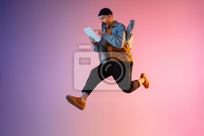 Plakat Full length portrait of happy jumping man wearing casual clothes in neon light isolated on gradient background. Emotions, ad concept. Using tablet, hurrying up, late for work or sale, shopping.