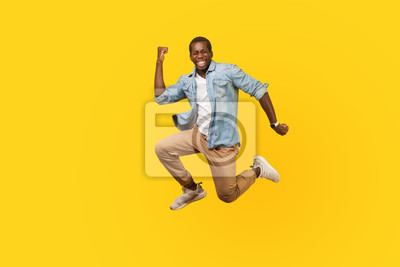 Plakat Full length portrait of joyous ecstatic man in denim shirt jumping for joy or flying with raised hand, gesturing yes i did it, celebrating success. indoor studio shot isolated on yellow background