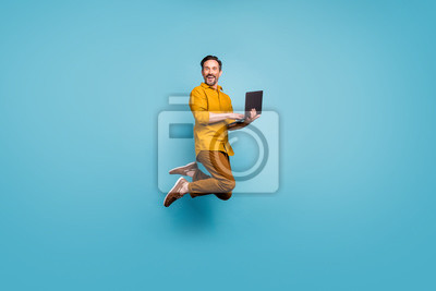 Plakat Full size photo of funky man feel rejoice emotions jump use laptop search social media online black friday discounts wear casual style clothing isolated over blue color background