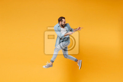 Plakat Funny young bearded man in casual blue shirt posing isolated on yellow orange background, studio portrait. People emotions lifestyle concept. Mock up copy space. Jumping pointing index fingers aside.