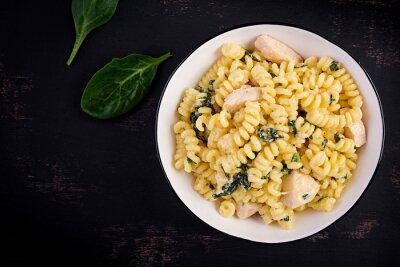Fusilli pasta with a creamy sauce with chicken meat, parmesan cheese and spinach on a bowl on a dark background.  Top view, copy space