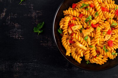 Fusilli pasta with chicken and sweet pepper in tomato sauce. Italian Cuisine. Top view, flat lay, overhead