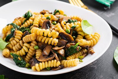 Fusilli pasta with spinach and mushrooms on a white plate. Vegetarian / vegan  food. Italian cuisine.