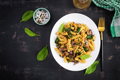 Fusilli pasta with spinach and mushrooms on a white plate. Vegetarian / vegan  food. Italian cuisine. Top view, flat lay, copy space