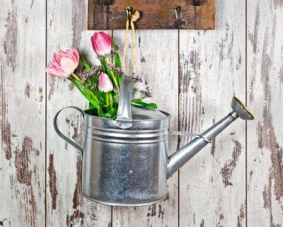Plakat Gießkanne mit Blumenstrauß vor Heller, verwitterter Holwand