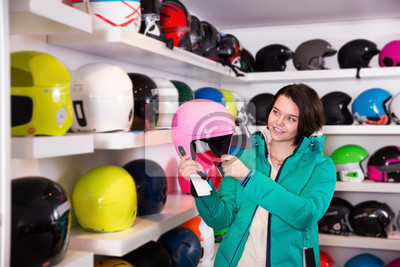 Plakat Girl choosing new skiing helmet in shop of sports ...