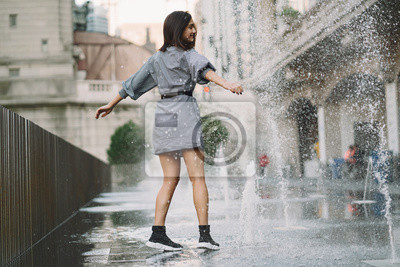 Plakat girl playing and dancing around on a wet street of Chicago