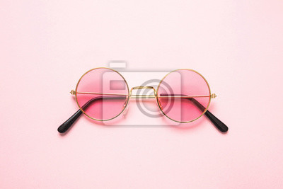 Plakat Golden frame sunglasses with pink lens on pink background, top view