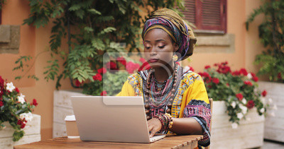 Plakat Good looking young African woman in the traditional clothes working on the laptop computer, tapping and texting, while sitting at the table in the nice yard outdoor.