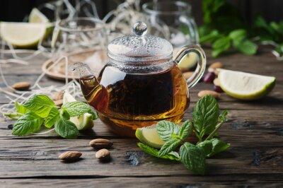 Plakat Gorąca herbata czarna z cytryną i miętą na drewnianym stole