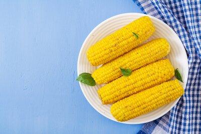 Gotowana kukurudza w bielu talerzu na błękitnym tle. Letnie jedzenie. Widok z góry. Leżał płasko